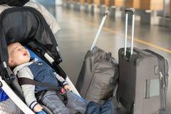 Het gillen de zitting van de babyjongen in wandelwagen dichtbij bagage bij luchthaventerminal Kind in het bureauteller van de ver royalty-vrije stock foto's