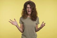 Het gillen verstoorde donkerbruine jonge die vrouw, in woede met haar vriend, over gele achtergrond wordt gekregen stock afbeeldingen