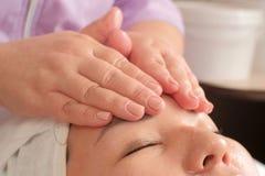 Het gladmaken van rimpels op het gezicht van de vrouw Close-up van massage op het vrouwelijke voorhoofd Gezicht en lichaamsverzor stock afbeeldingen