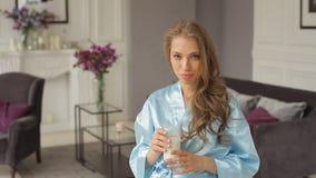 Het glamourmeisje in blauwe toga komt dichter en drinkt melk stock videobeelden