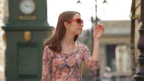 Het glamourmeisje gaat langs een steeg en stijgt haar zonglazen op ziend een vriend in slo-mo stock footage