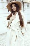 Het glamourmeisje met donker recht haar draagt luxueuze beige laag met elegante hoed, Stock Afbeeldingen