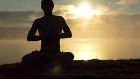 Het glanzen de mens zit op een meerbank, bidt en praktijkenyoga bij zonsondergang in langzame motie stock videobeelden