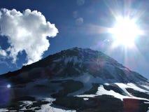 Het glanzen van de zon, sneeuwberg en wolken Stock Afbeelding