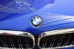 Het glanzende embleem van ` BMW ` op een blauwe autokap met chroomgrill stock afbeeldingen