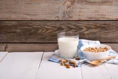 Het glas amandelmelk met amandelen verspreidde zich rond op een houten oppervlakte met een doekservet Concept van lactose het vri royalty-vrije stock foto