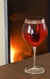 Het glas dichtbij de open haard Stock Foto
