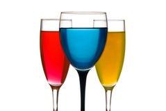 Het glas en de champagneglazen van de wijn. Kleurrijke vloeistof Stock Foto's