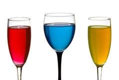 Het glas en de champagneglazen van de wijn. Kleurrijke vloeistof Stock Afbeeldingen