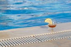 Het glas geurige cognac met een plak van citroen bevindt zich bij de rand van de pool royalty-vrije stock afbeelding