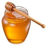 Het glas kan hoogtepunt van honing en houten stok op het stock foto