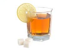 Het glas met een plak van citroen vulde met citroenthee en raffineerde su Royalty-vrije Stock Foto's