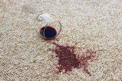 Het glas rode wijn viel op tapijt stock foto
