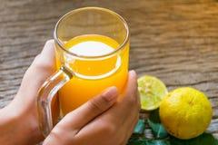 Het glas van de handholding jus d'orange voor het drinken Royalty-vrije Stock Foto's