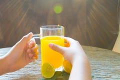 Het glas van de handholding jus d'orange voor het drinken Stock Foto's