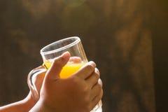 Het glas van de handholding jus d'orange voor het drinken Royalty-vrije Stock Fotografie