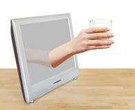 Het glas van de handholding melk leunt TV-uit het scherm Royalty-vrije Stock Foto