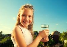 Het glas van de kindholding met water stock afbeeldingen