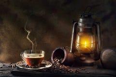 Het glas van de koffiekop en uitstekende de olielantaarn die van de kerosinelamp w branden stock afbeeldingen