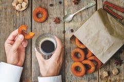 Het glas van de mensenholding van koffie en pompoendoughnut Royalty-vrije Stock Afbeeldingen