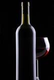Het Glas van de rode Wijn binnen achter Fles Royalty-vrije Stock Afbeeldingen