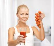Het glas van de vrouwenholding sap en tomaten Stock Fotografie