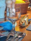Het glas van de wijn in eettafel Stock Foto