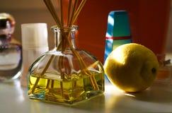 Het glas van geurdiffusor met rietstokken tussen parfum die flacons natuurlijke geur van citroen geven stock afbeelding