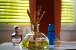 Het glas van geurdiffusor met rietstokken tussen parfum die flacons natuurlijke geur van citroen geven stock foto's