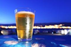 Het glas van het bier dat bij zonsondergang wordt gekoeld die stad overziet ligh Stock Foto