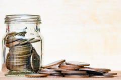 Het glas van muntstuk en uitgespreid muntstuk op vloer op uitstekend hout vertroebelde B Royalty-vrije Stock Afbeeldingen