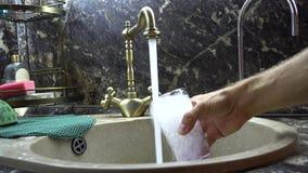 Het glas wordt gewassen met water in een gootsteen stock footage