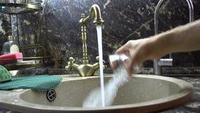 Het glas wordt gewassen met water in een gootsteen stock video