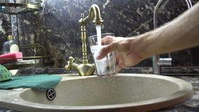 Het glas wordt gewassen met water in een gootsteen stock videobeelden