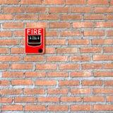Het het glasalarm van de brandonderbreking schakelt bakstenen muurachtergrond in stock afbeelding