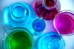 Het glaswerk die van het chemielaboratorium roze, blauwe en groene oplossingen op een nadenkende oppervlakte en een periodieke li royalty-vrije stock afbeelding