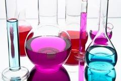 Het glaswerk van het laboratorium met kleurrijke chemische producten Stock Foto's