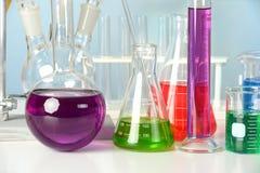 Het glaswerk van het laboratorium met vloeistoffen Stock Afbeelding