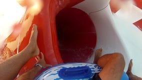Het glijden onderaan de buis in aquapark stock videobeelden