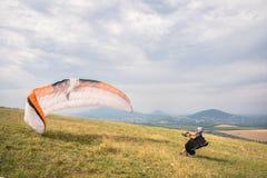 Het glijscherm opent zijn valscherm alvorens van de berg in de Noord-Kaukasus op te stijgen Het vullen van de valschermvleugel stock foto