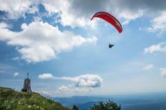 Het glijscherm vliegt over de heuvels met een mooie kerk op een zonnige dag Royalty-vrije Stock Foto