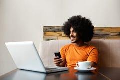 Het glimlachen Afrikaanse Amerikaanse mensenzitting bij lijst met mobiele telefoon Stock Foto's