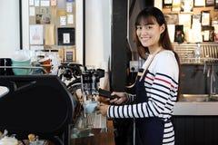 Het glimlachen Aziatische barista die cappuccino met koffiemachine voorbereiden royalty-vrije stock foto's