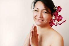 Het glimlachen Aziatische schoonheid met orchideeën Royalty-vrije Stock Afbeeldingen
