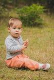 Het glimlachen babyzitting in het bos Royalty-vrije Stock Afbeeldingen
