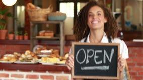 Het glimlachen barista die een open uithangbord houden stock footage