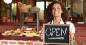 Het glimlachen barista die een open uithangbord houden stock videobeelden