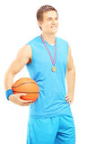 Het glimlachen basketbalspeler het stellen met gouden medaille en basketbal Stock Fotografie
