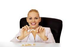 Het glimlachen bedrijfsvrouwenzitting achter het bureau en de brekende sigaret stock foto's