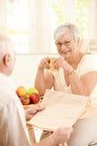 Het glimlachen bejaarde vrouwenzitting bij lijst met mok royalty-vrije stock foto